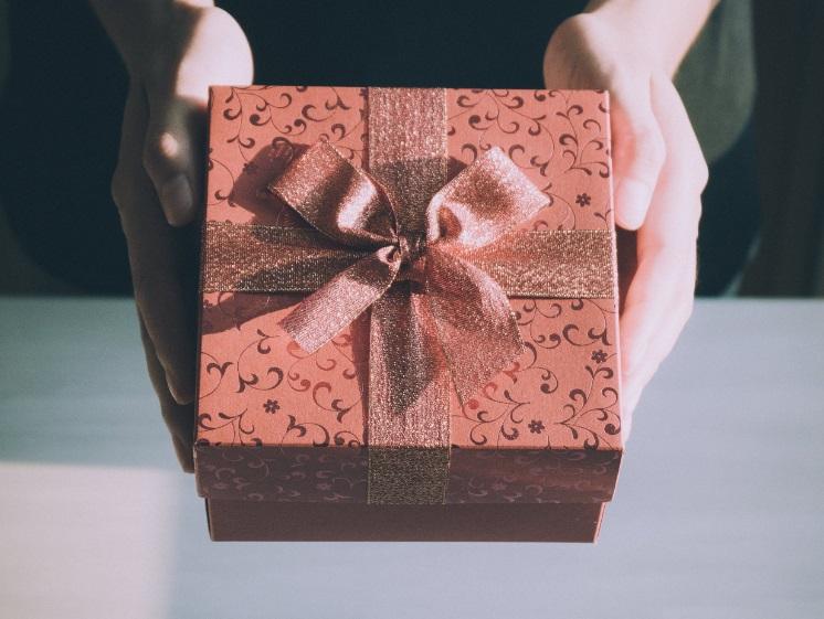 Mains qui tendent un cadeau
