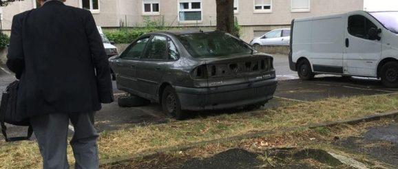Homme devant voiture épave sur un parking