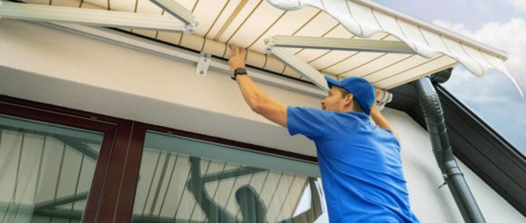 Homme répare un store