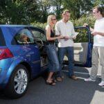 Trois personnes à côté d'une voiture bleue