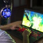 Un homme entrain de jouer sur son ordinateur avec un casque