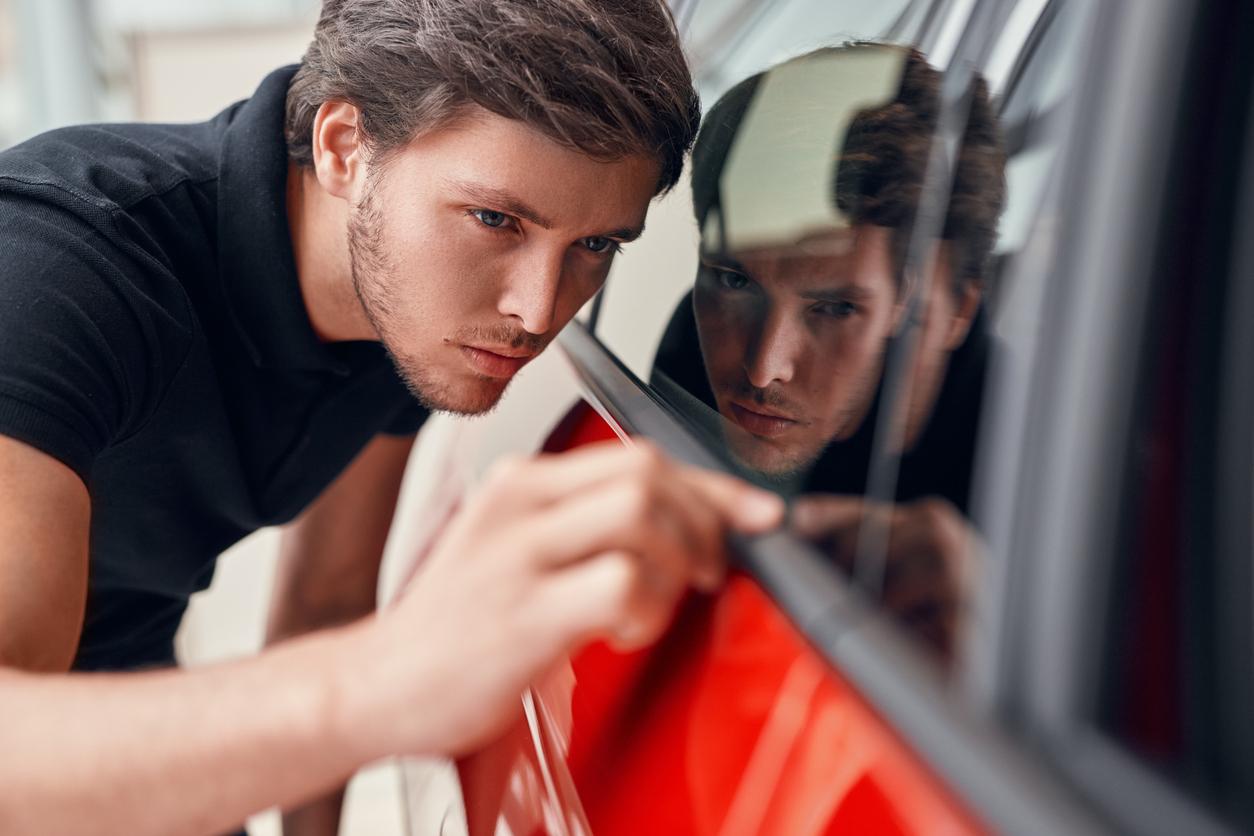 Un homme qui inspecte une voiture pour voir si il n'y a pas de rayures
