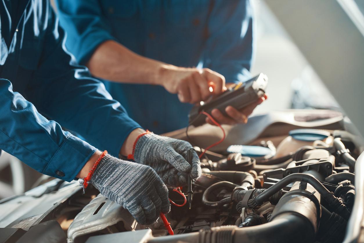 Deux personnes entrain de reprogrammer le moteur d'une voiture