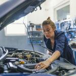 Une garagiste entrain de réparer le moteur d'une voiture
