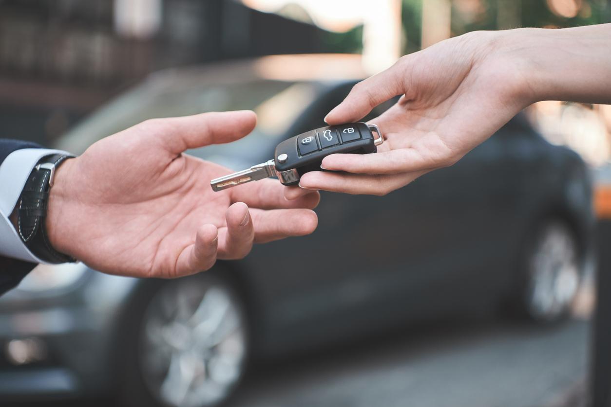 Une personne donnant des clés de voiture à une autre personne