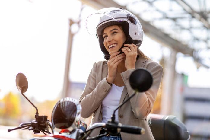 une jeune femme sur moto souriante