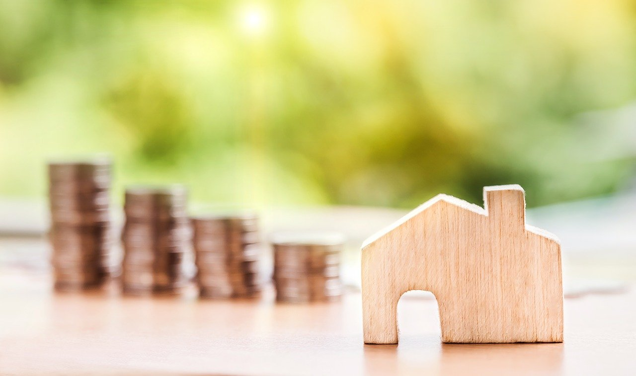 maison en bois devant pièces de monnaie en pile