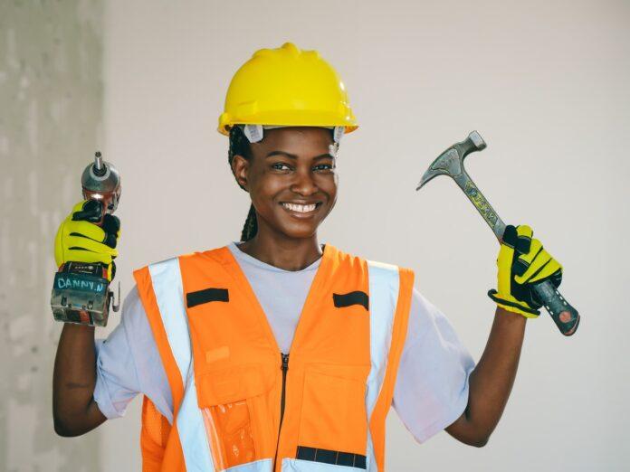 jeune femme équipement de chantier perceuse et marteau en mains