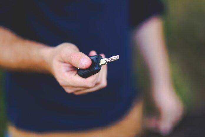 main homme tend clé de voiture d'occasion
